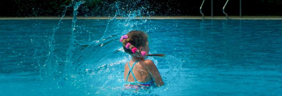Mädchen planscht im Schwimmbecken