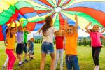 Lachende Kinder strecken die Arme in die Luft draußen im Sommer