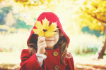 Kind in einem roten Mantel. Hält sich ein Laubblatt vor das Gesicht und lacht.