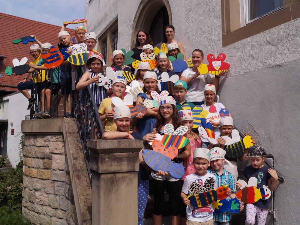 Kinder in der Sommerferienbetreuung basteln bunte Remsis