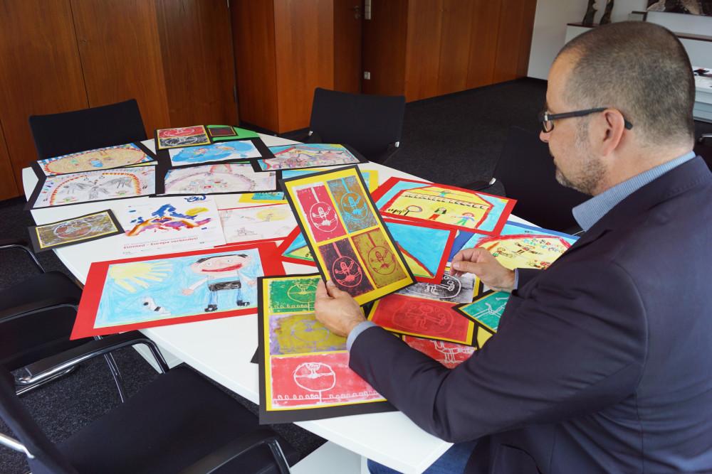 OB Scharmann schaut sich Bilder des Malwettbewerbs an