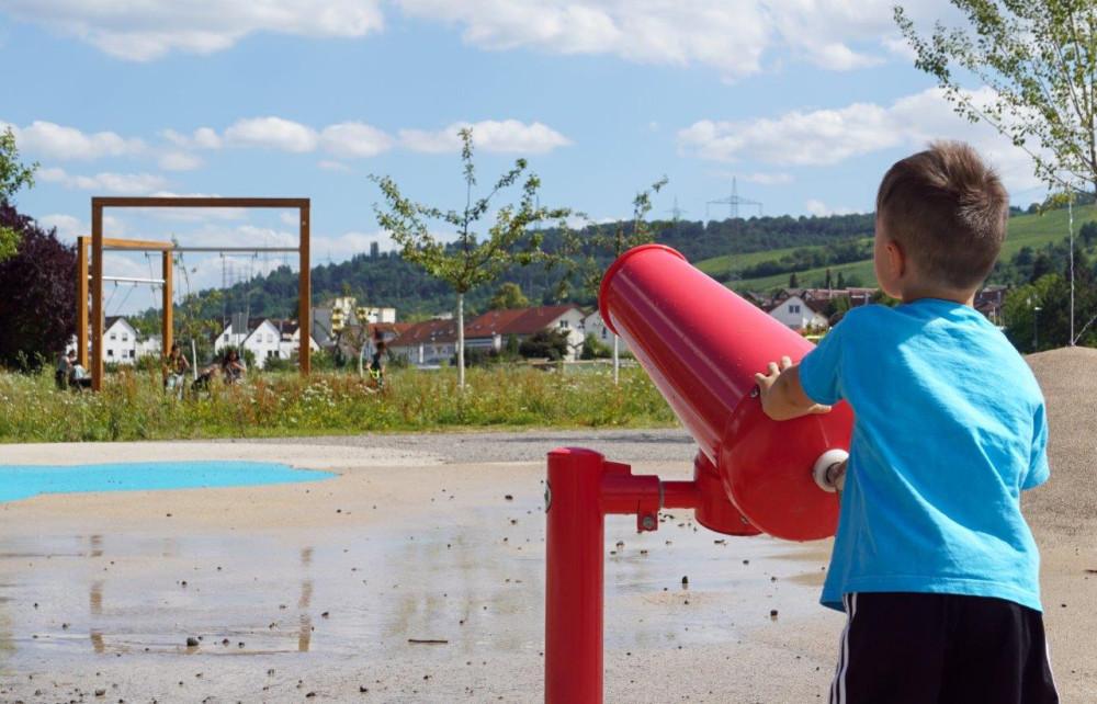 Ein Junge spielt am Wasserspielplatz